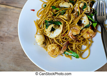 Spicy paghetti with seafood on wooden table.