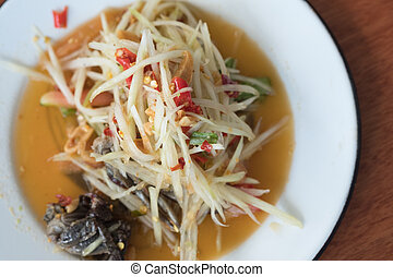 Spicy papaya salad or Som Tum in Thailand on white plate
