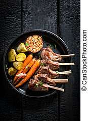 Spicy roasted lamb ribs on dark background