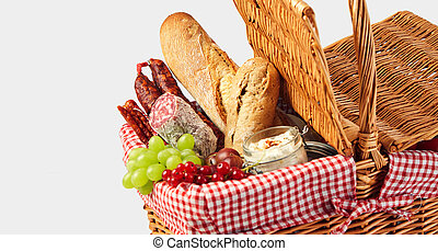Spicy sausages, fresh fruit and baguettes in a wicker picnic...