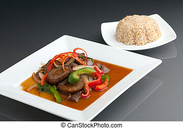 A beautifully presented dish of Thai food with mixed vegetables beef and brown rice.