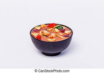 Spicy Thai soup Tom Yam with seafoodon in a black bowl on a white background