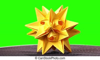 Spiked origami figure of yellow color. Origami cosmic body...