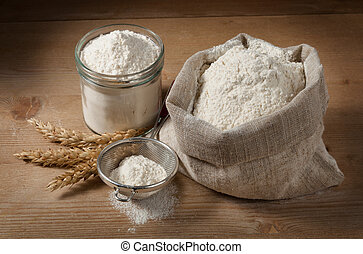 Spikelets and flour in the bag, jar on the boards