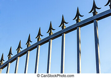Spikes on Galvanised Gate Against Blue Sky - Security pikes...
