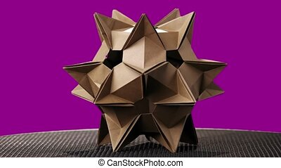 Spiky origami figure on colorful background. Celestial body...