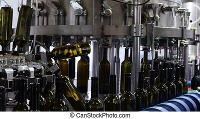 Spill of alcohol wine in glass bottles at the plant. Conveyor belt with glass bottles. The production process of alcoholic beverages. 4K res.