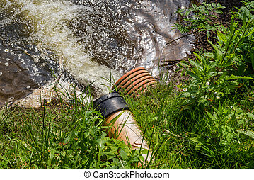 Spill water  in a lake - Pipe with spill water at a lake