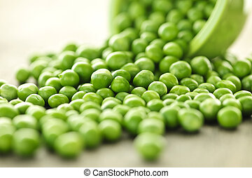 Spilled bowl of green peas - Closeup on spilling bowl of...