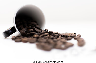 Spilled coffee beans from the white ceramic cup isolated on white background, cup spilled with coffee beans