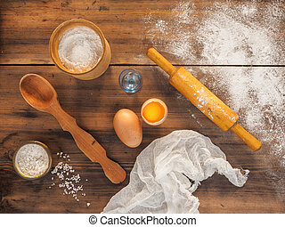 Spilled flour, salt, egg yolk, fabric, wooden spoon and rolling pin. Still life on the background of the old wooden table, top view in rustic style with kitchen utensils