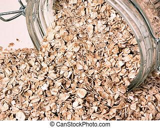 Glass jar of full of raw oats spilt over on side.