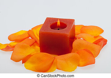 Spilled petals of the orange-rose around the aromatic candle