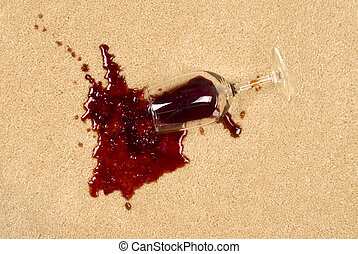 Spilled wine on carpet - A glass of spilled wine on brand...