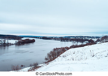 Spilling river in winter against the backdrop of a beautiful snow-covered forest. White hills in distance. Clean nature in the fresh air.