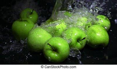 Spilling water over green apples super slow motion shot
