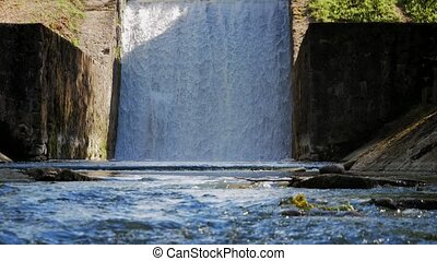 Spillway on the river. The flow of water falls down