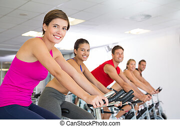 Spin class working out and smiling at camera at the gym