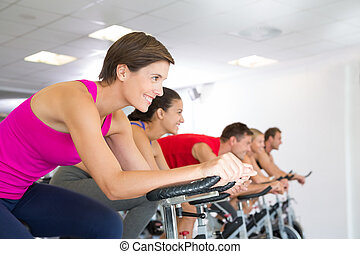 Spin class working out and smiling at the gym