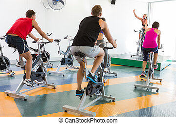 Spin class working out with motivational instructor at the...