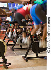 spin the bike - blur motion of group of people having a...