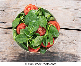 spinach and tomato salad on a wooden table. top view