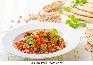 Spinach chickpea curry, fresh and healthy, with herbs and lebanese bread