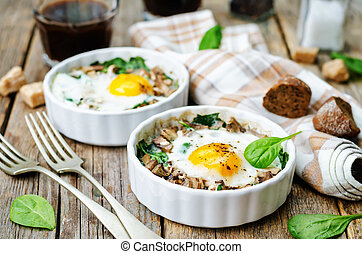 spinach, mushrooms baked egg on a dark wood background. ...