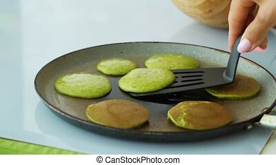 Spinach pancakes on cooking pan. Healthy breakfast.