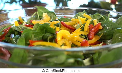 Spinach salad with tomatoes, adding colorful bell pepper and red onion, rotating, zoom in