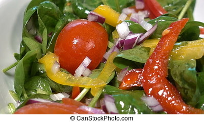 Spinach salad with tomatoes and bell pepper, close up, rotating, zoom in