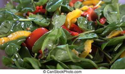 Spinach salad with tomatoes and bell pepper rotating, close...