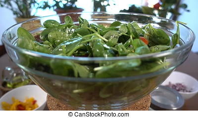 Spinach salad with tomatoes and bell pepper rotating,...