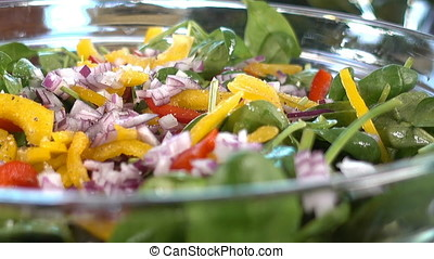 Spinach salad with tomatoes and bell pepper, seasoning with salt, pepper and olive oil, panning