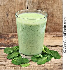 Spinach smoothie with young leaves spinach on wooden tables
