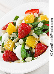 Spinach, strawberry, orange, quail eggs salad with almonds slices and balsamic vinegar on white plate