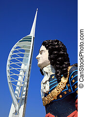 The millennium Spinnaker Tower in Gunwharf Quays, Portsmouth Harbour, one of the biggest paying tourist attractions in the South of England with an old historic ships figurehead in the foreground