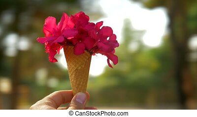 Spinning around with summer red bouquet in waffle cone -...