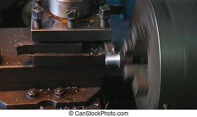 Spinning cylinder on a lathe machine cutting metallic chips...