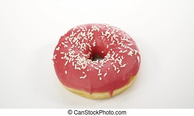 spinning donut with pink icing on a white background