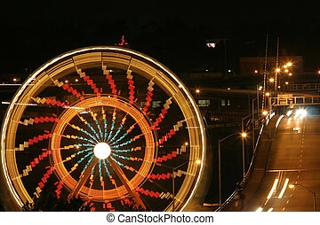 Spinning Ferris Whee - A Ferris Wheel spinning near a busy...
