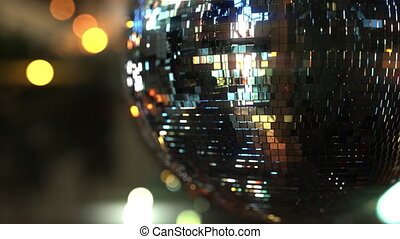 Spinning mirror disco ball against bokeh background