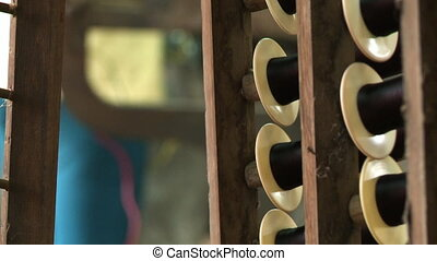 Spinning plastic thread spools on wooden supports - An...