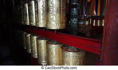 Spinning prayer wheels in buddhist monastery