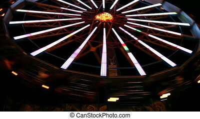 Colorful illuminated spinning wheel in amusement park at night