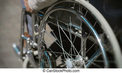 Spinning Wheels - Tilt up of wheelchair details with cropped...
