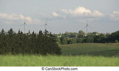 Spinning wind mill turbines in the distance surrounded by trees and grass. Rotating windmills in rural village surrounded by nature and clouds in the background