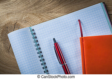 Spiral checked copybook notebook pen on wooden board