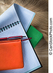 Spiral checked copybook notepads pen on wooden board