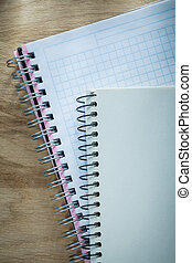 Spiral checked copybooks on wooden board